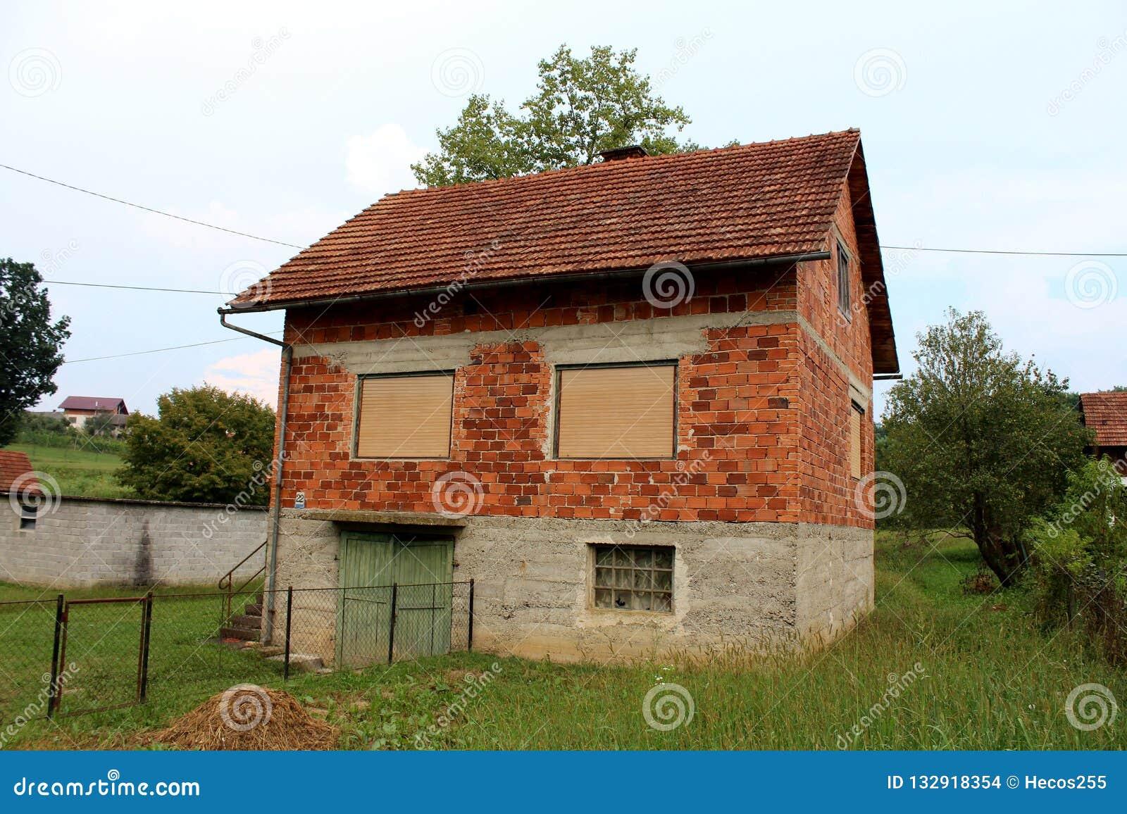 有闭合的窗帘和被毁坏的木车库门的未完成的被放弃的红砖家庭房子围拢与未割减