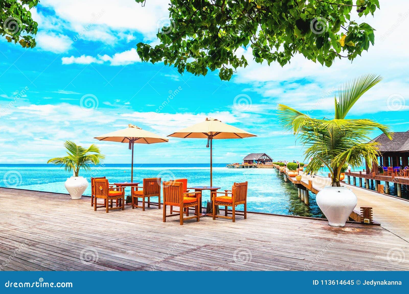 有阳伞的餐馆在反对海洋的天蓝色的水的一个木码头