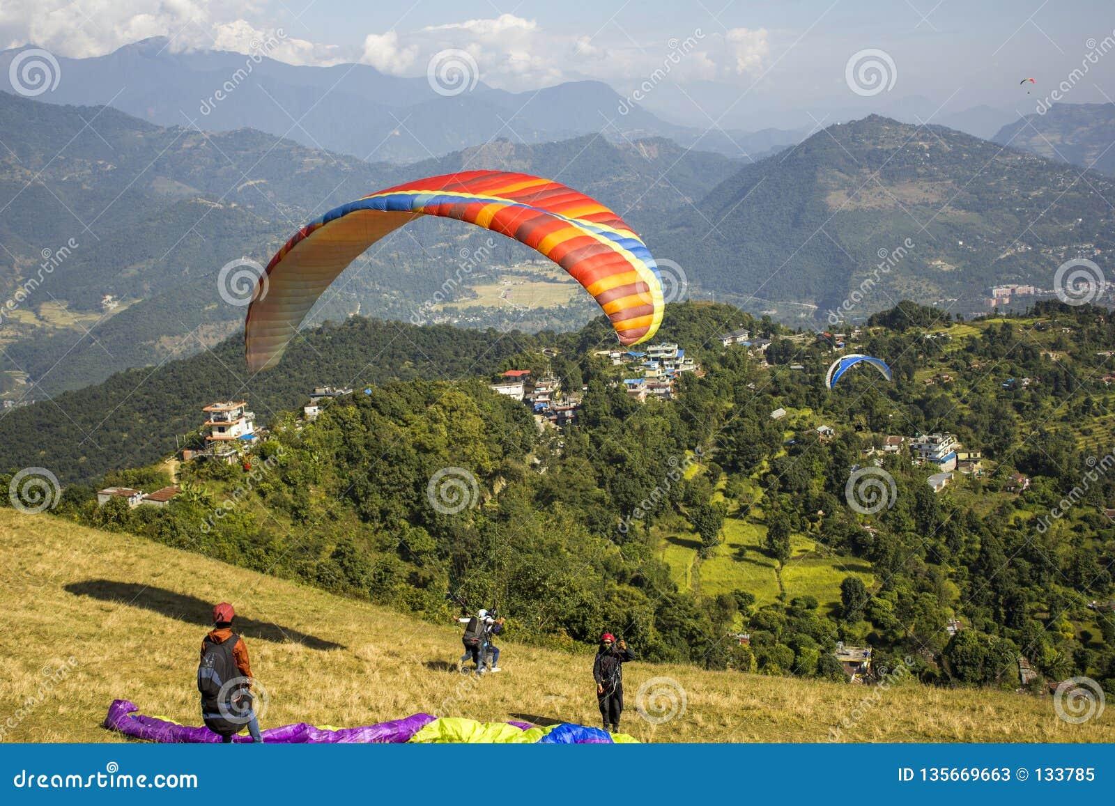 有降伞的几个滑翔伞在倾斜准备飞行,起飞的纵排奔跑反对绿色的背景