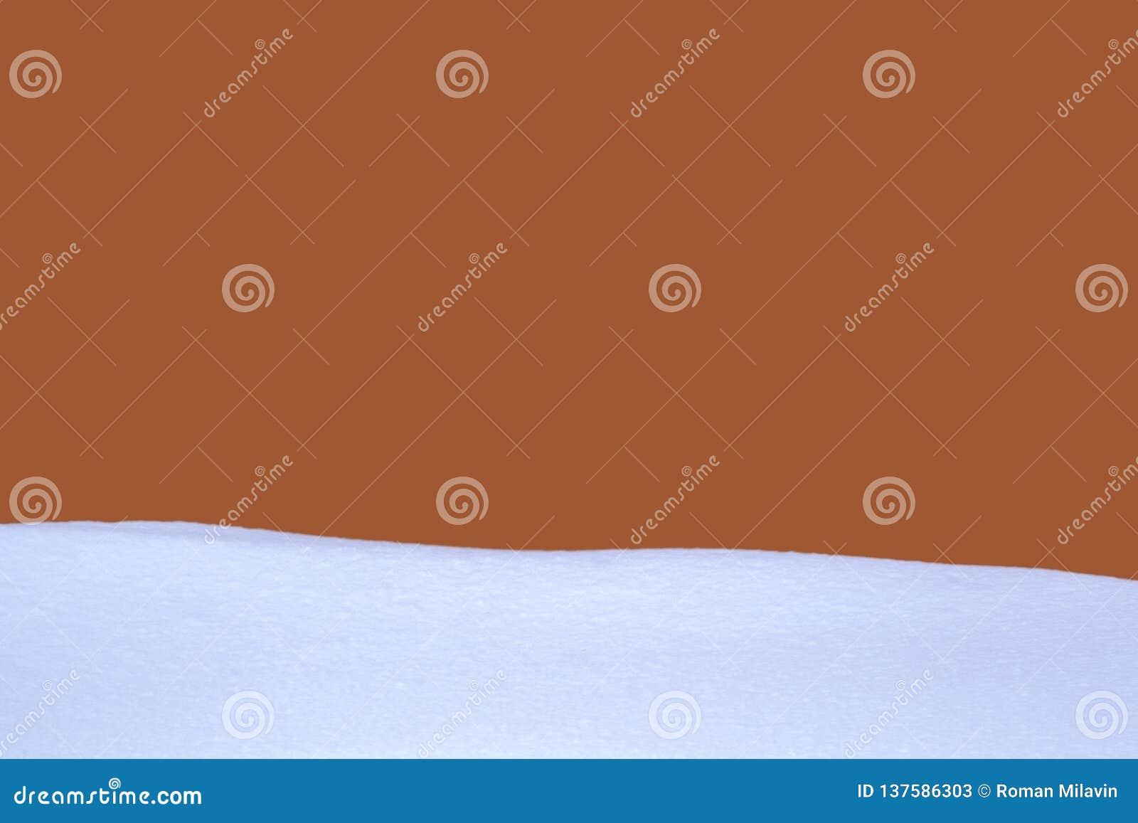 有雪的布朗墙壁在前景 红色墙壁