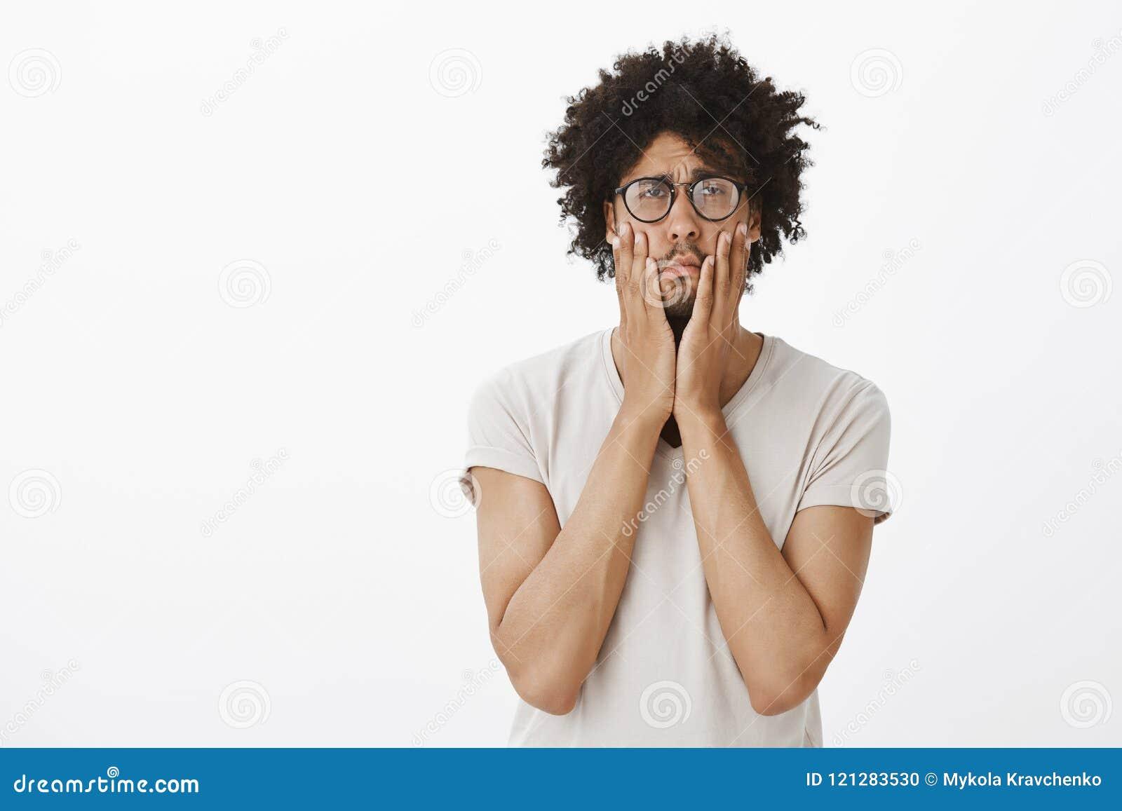 有非洲的理发的阴沉和生气逗人喜爱的人,紧压面颊用手和注视与哀伤和阴沉的表示