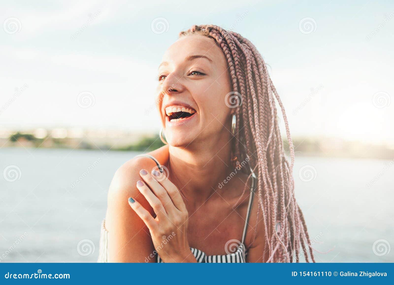 有非洲辫子的愉快的无忧无虑的年轻女人享有她的在海滩的生活,暑假时间