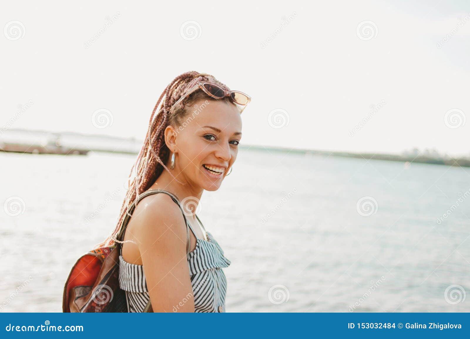 有非洲辫子的愉快的无忧无虑的年轻女人在太阳镜享有在海滩的生活,暑假时间