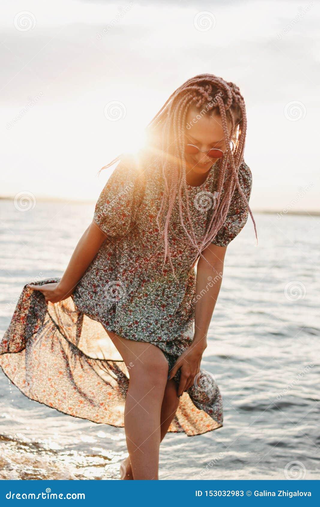 有非洲辫子的无忧无虑的年轻女人在海滩,暑假时间的美丽的礼服