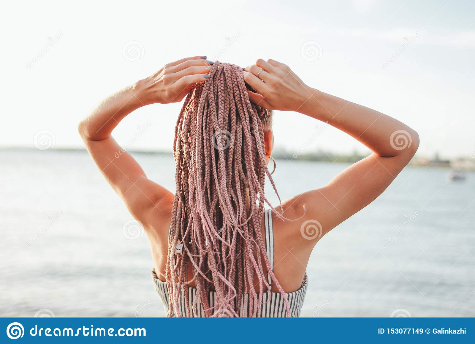 有非洲辫子的美丽的浪漫年轻女人在海滩,看法从后面,暑假时间的礼服