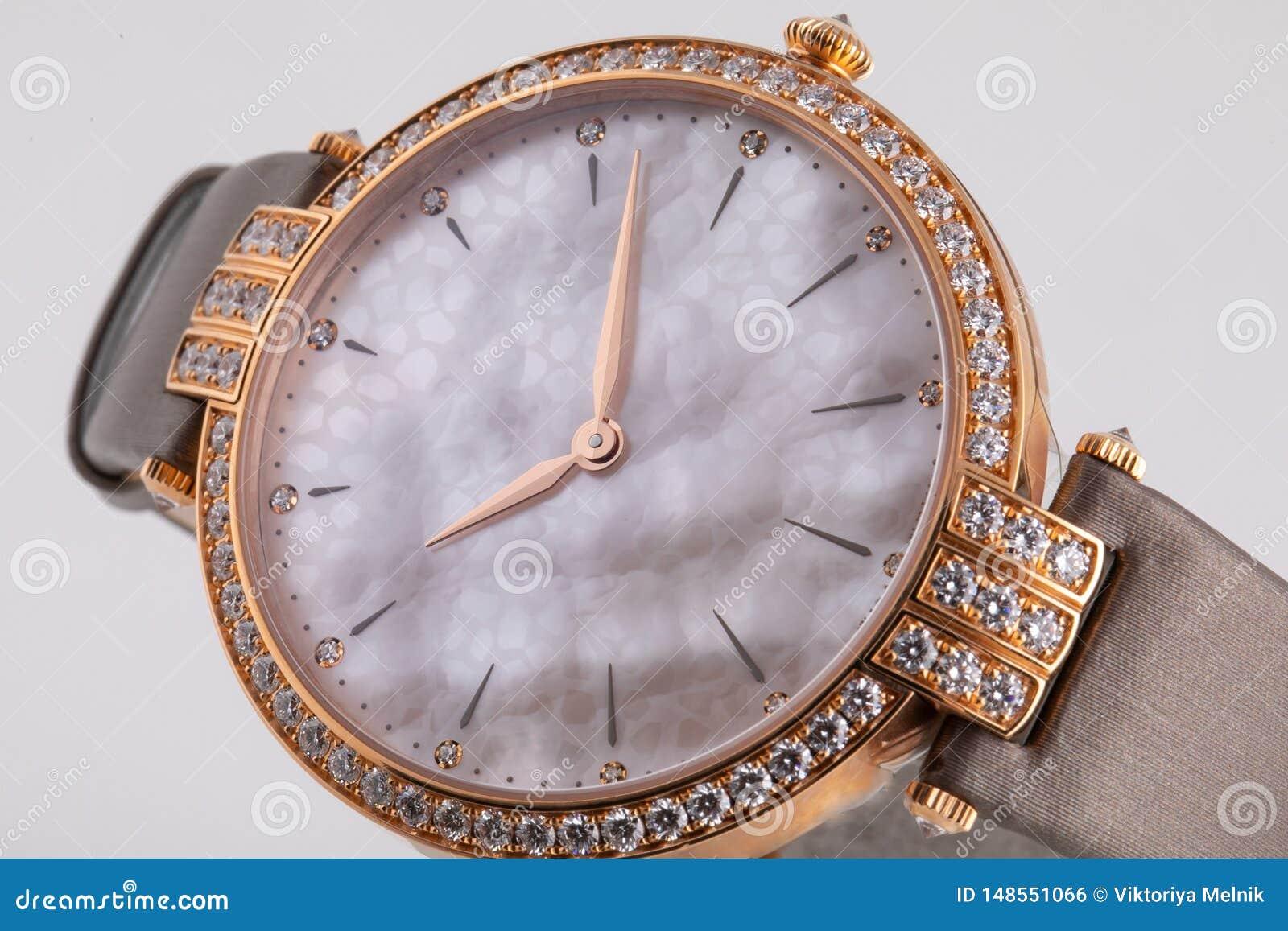 有顺时针方向一个灰色拨号盘的女性金表,金黄,构筑石头,与一条棕色布料皮带
