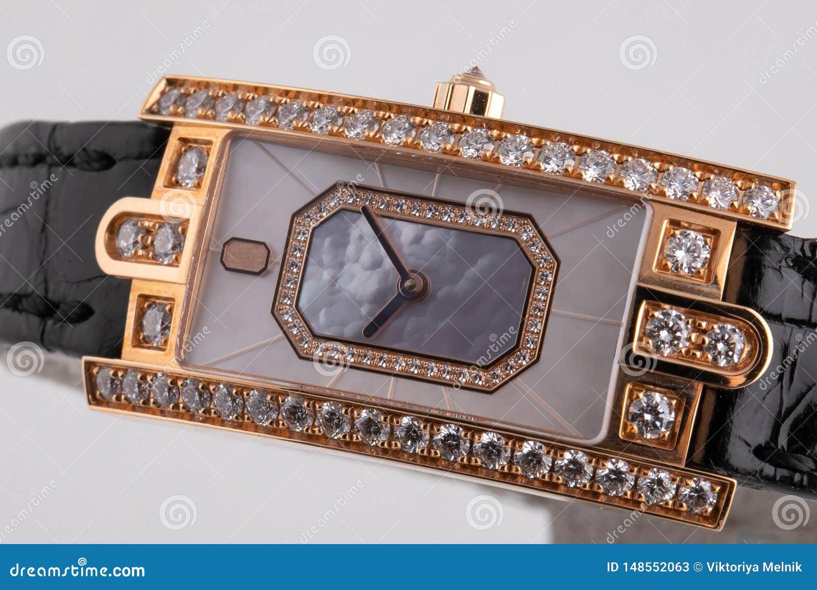有顺时针方向一个灰色拨号盘的女性金黄手表,黑,构筑石头,与黑皮带