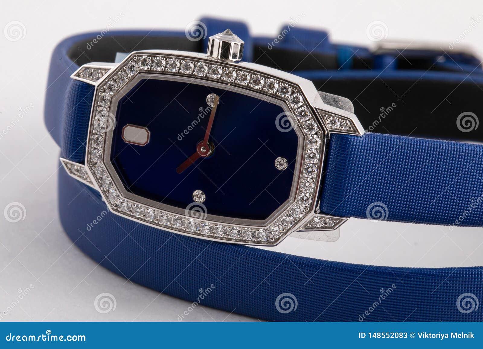 有顺时针方向一个蓝色拨号盘的女性银色手表,棕色,构筑石头,与一条蓝色布料皮带