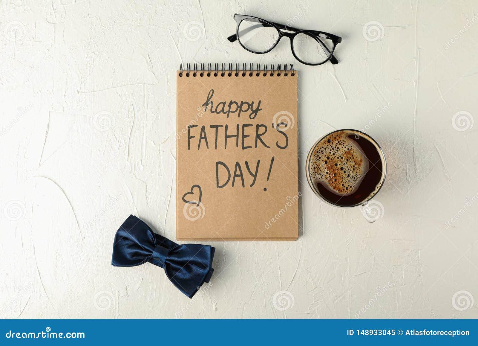 有题字愉快的父亲节、蓝色蝶形领结、咖啡和玻璃的笔记本在白色背景