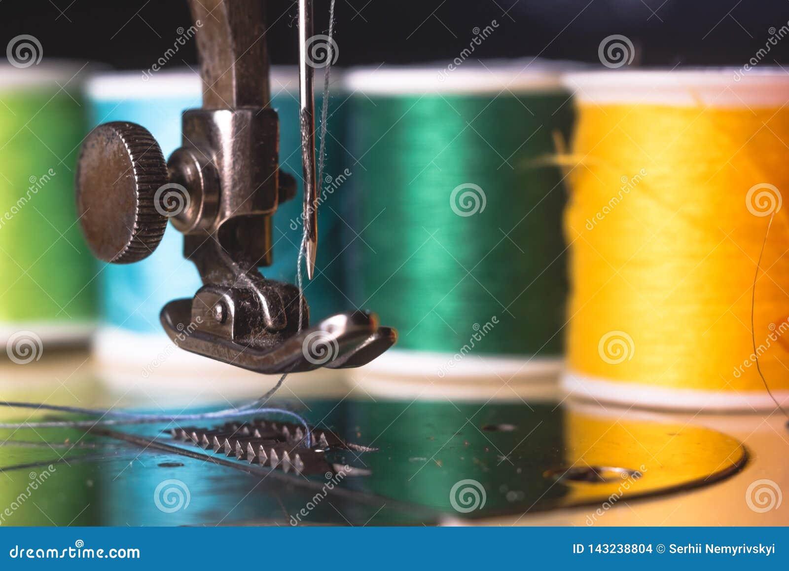 有颜色螺纹和针的老缝纫机,在一个老脏的工作表上 裁缝` s工作表 纺织品或美好布料做