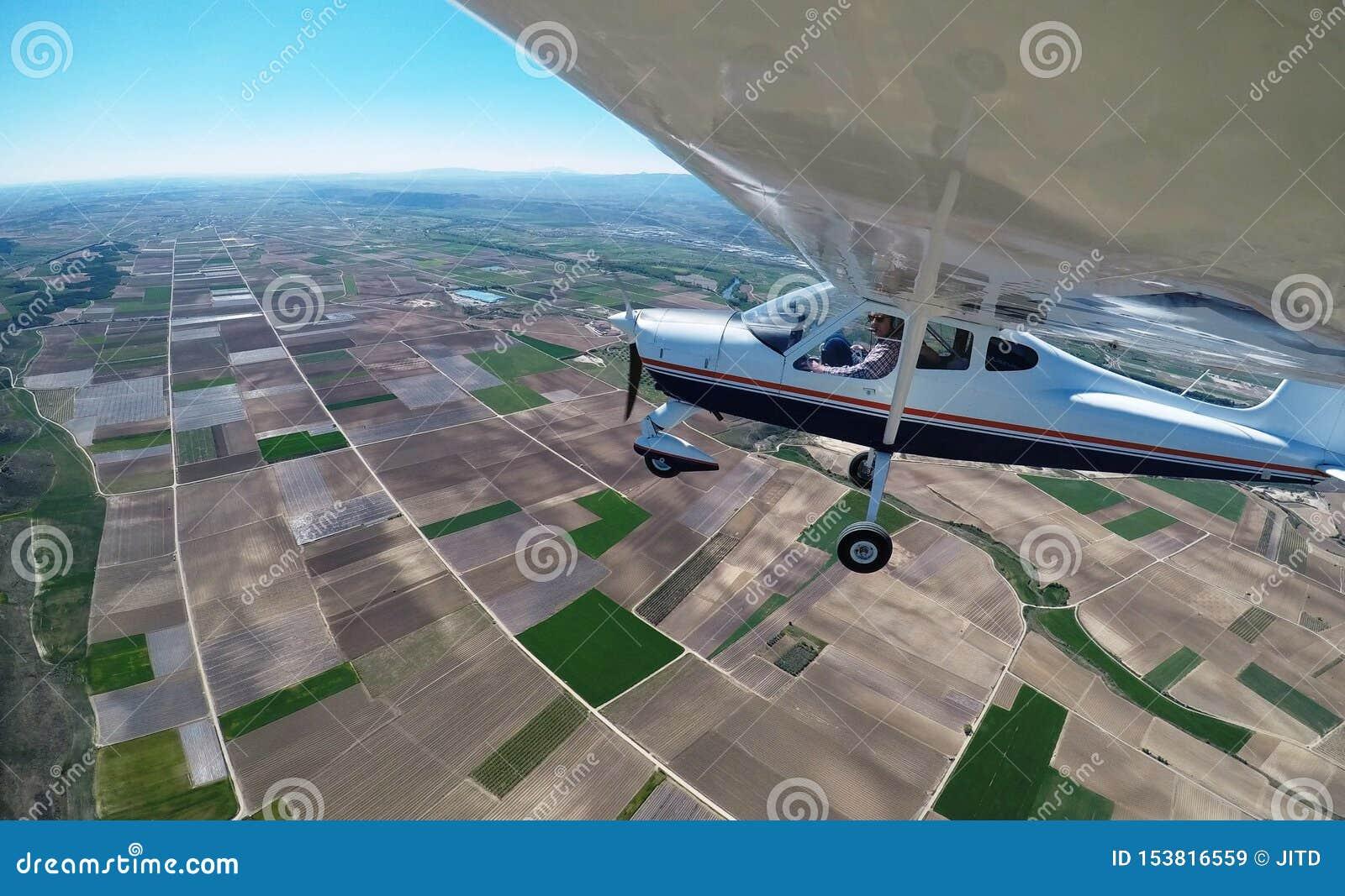 有飞机的试验飞越的农田选拔装有引擎和高翼的飞机