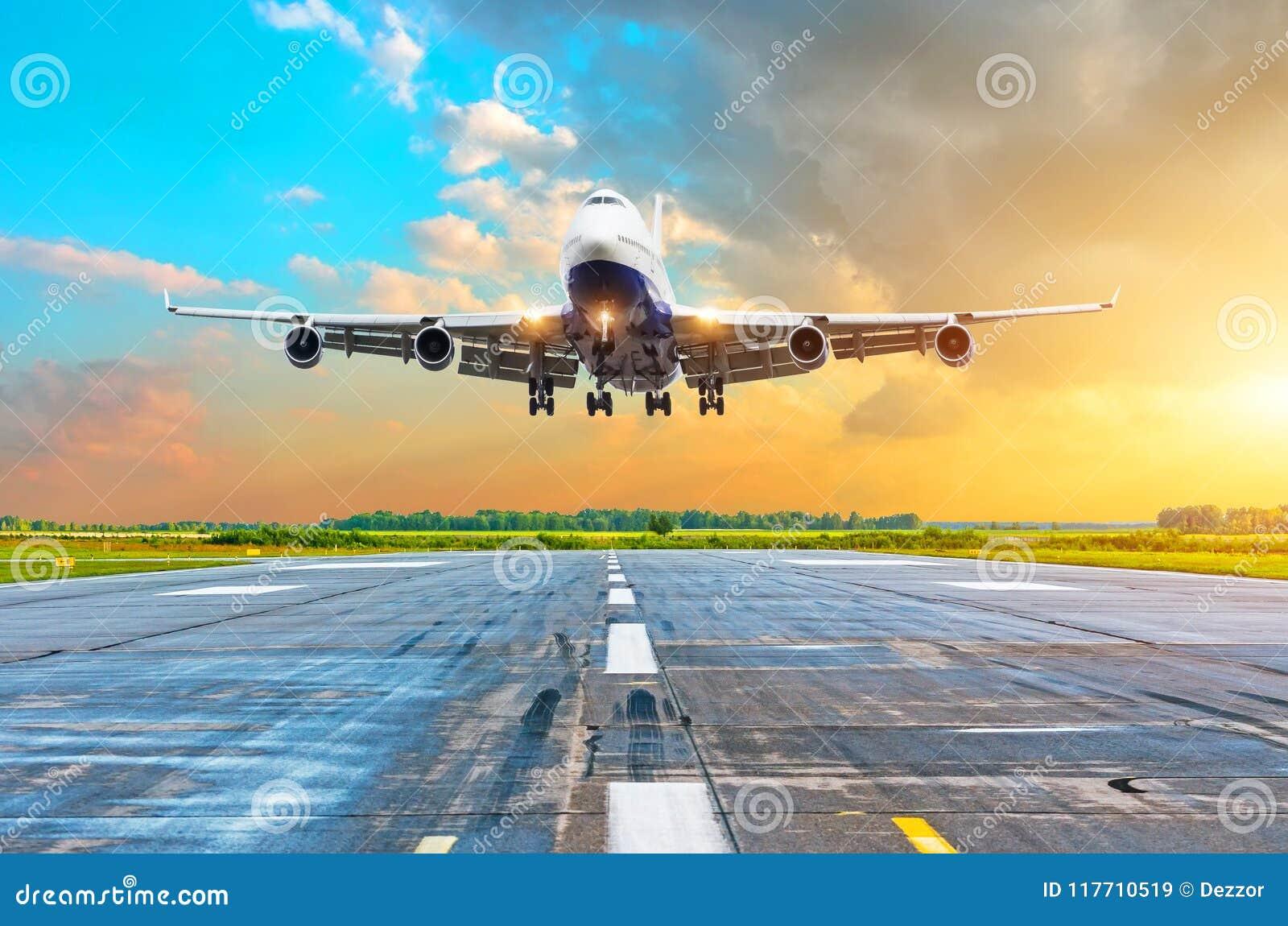 有飞行在一条跑道的四个引擎的航空器到来着陆在晚上在明亮的红色梯度日落期间