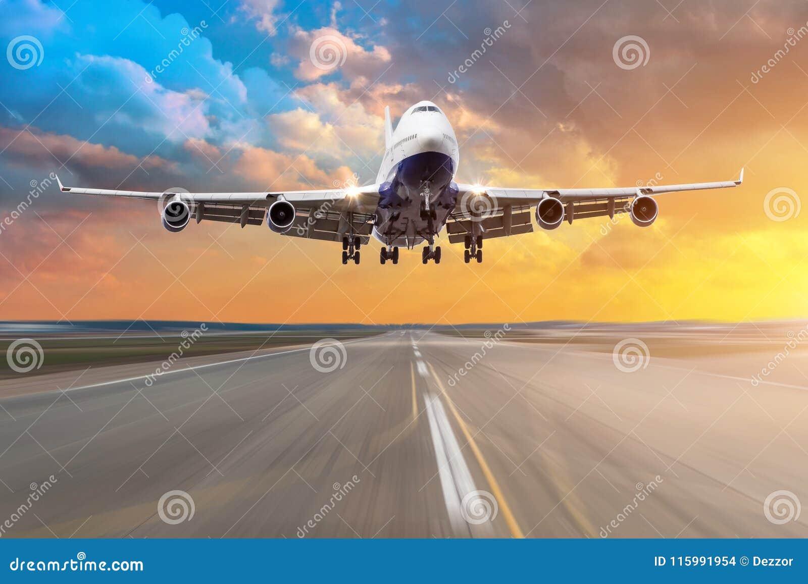 有飞行在一条跑道的四个引擎的飞机到来着陆在晚上在明亮的红色日落期间