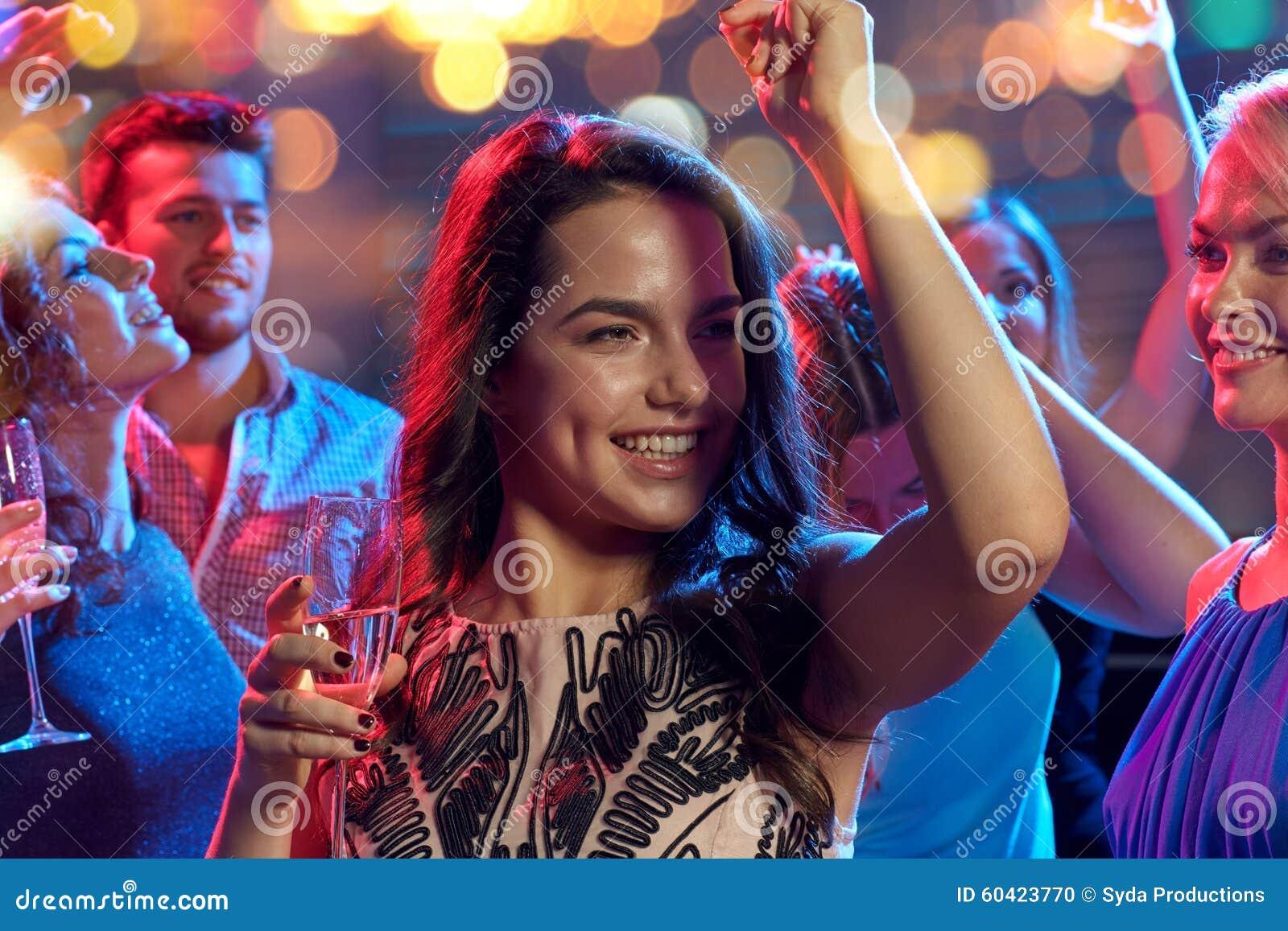 有香槟跳舞的愉快的朋友在夜总会