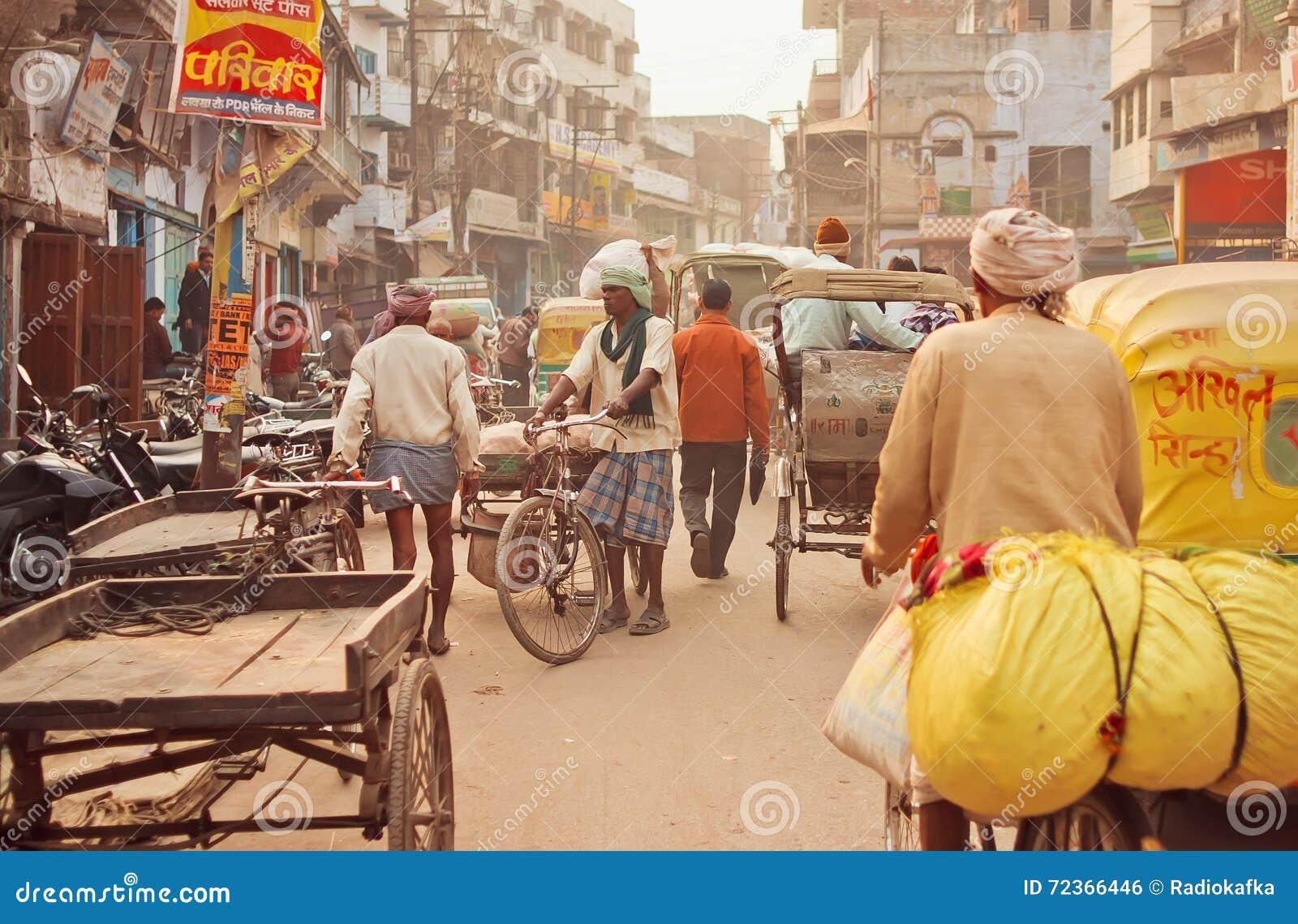 有驾驶通过老大厦的货物工作者和骑自行车者的拥挤街道