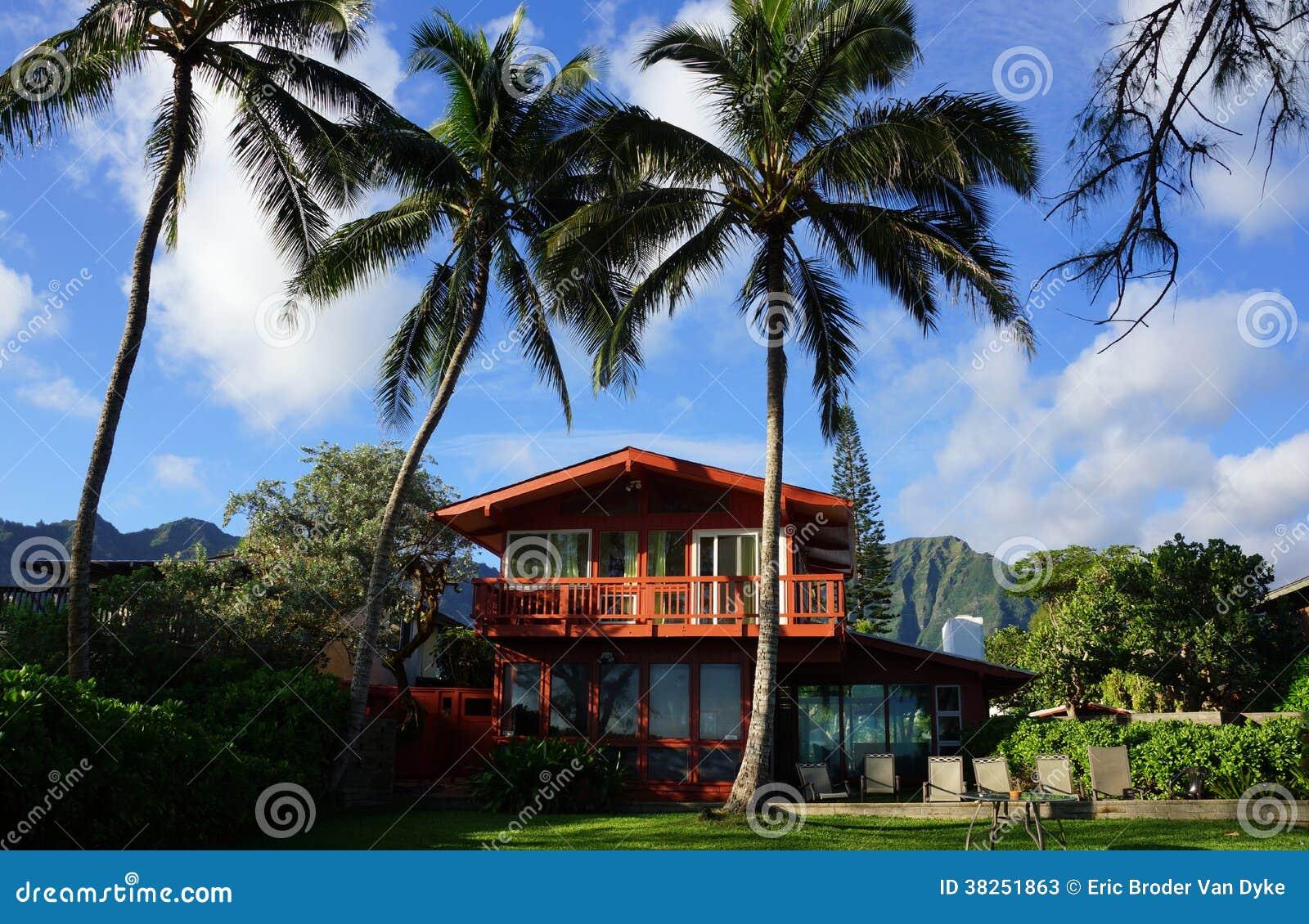 有高椰子树的红色二层的海滨别墅