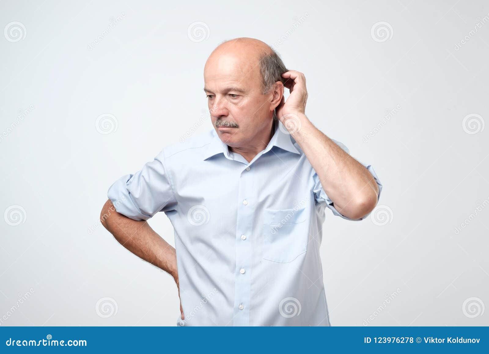 有髭的秃头成熟人在蓝色衬衣遭受犹豫不决