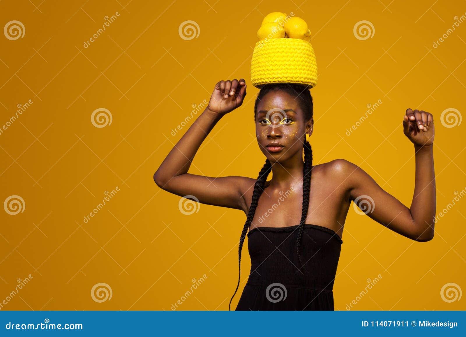 有黄色构成的快乐的年轻非洲妇女在她的眼睛 反对黄色背景的女性模型用黄色柠檬