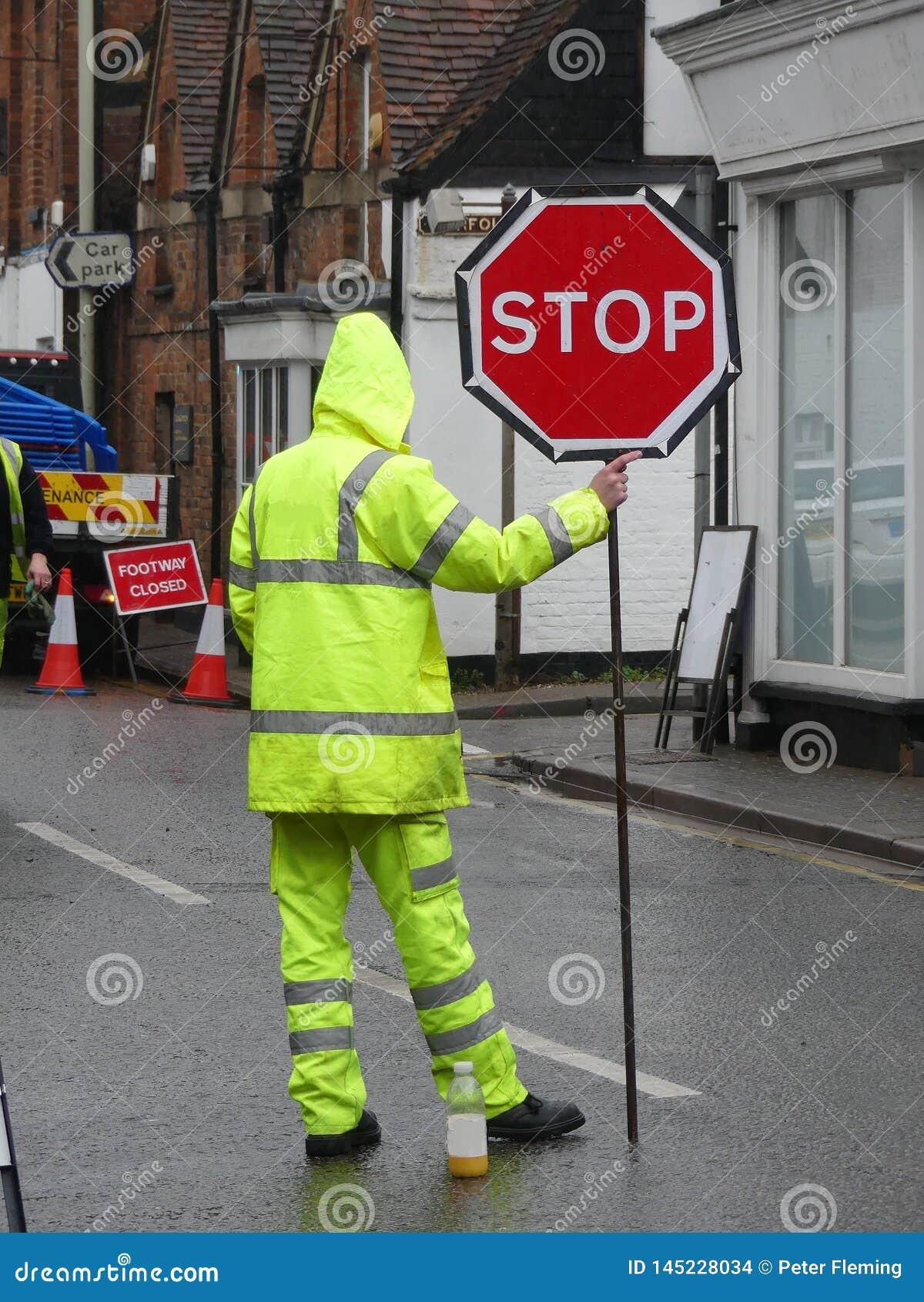 有黄色萤光拿着中止红色标志的夹克和长裤的男性路工作者
