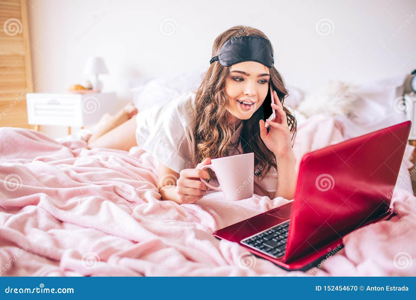 有黑发的年轻女人 谈话在电话和看在膝上型计算机屏幕上 在手中杯 单独在卧室 说谎在床上