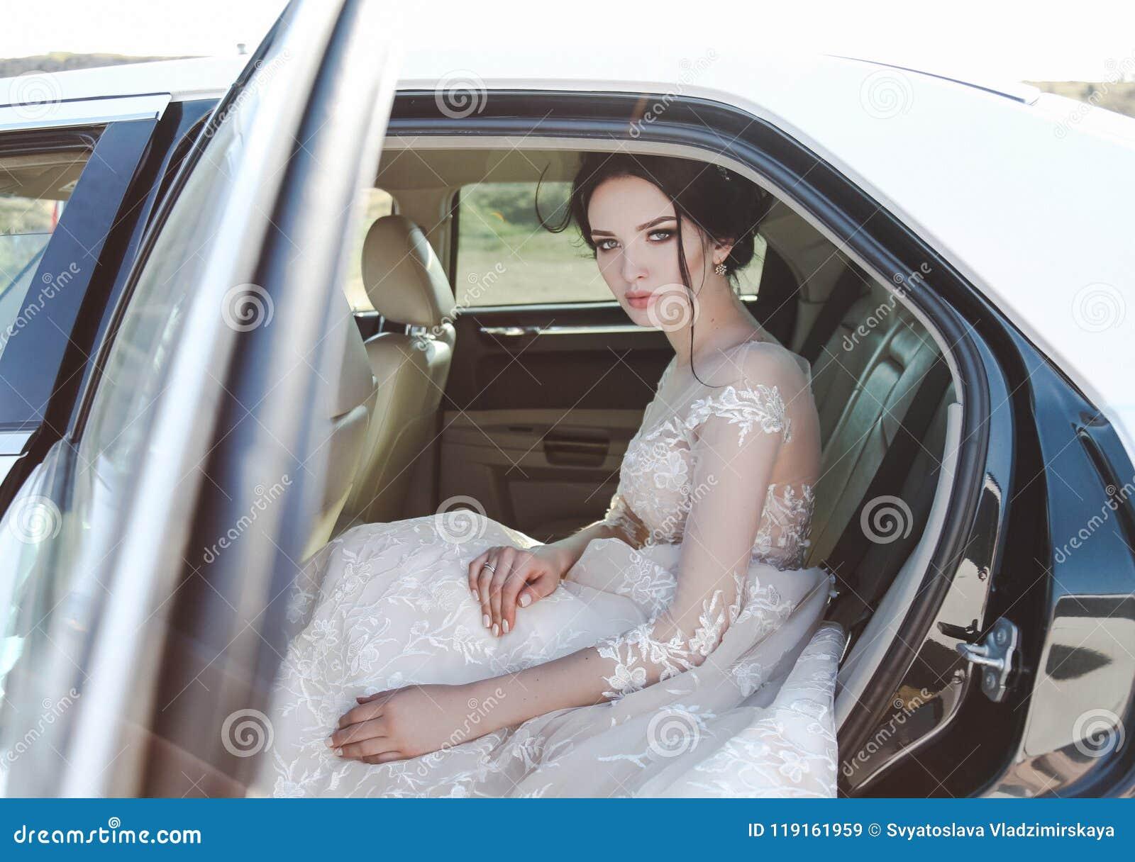 有黑发的美丽的新娘在典雅的婚礼礼服,摆在