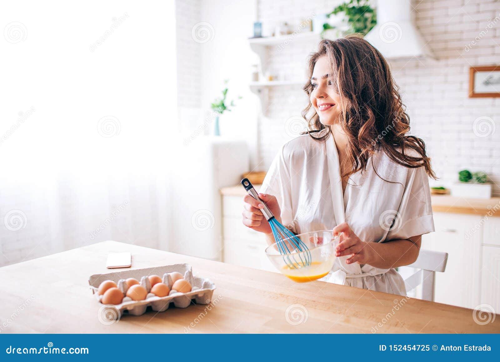 有黑发立场的年轻女人在厨房和烹调里 混和的鸡蛋 ?? 早晨白天 看平直和