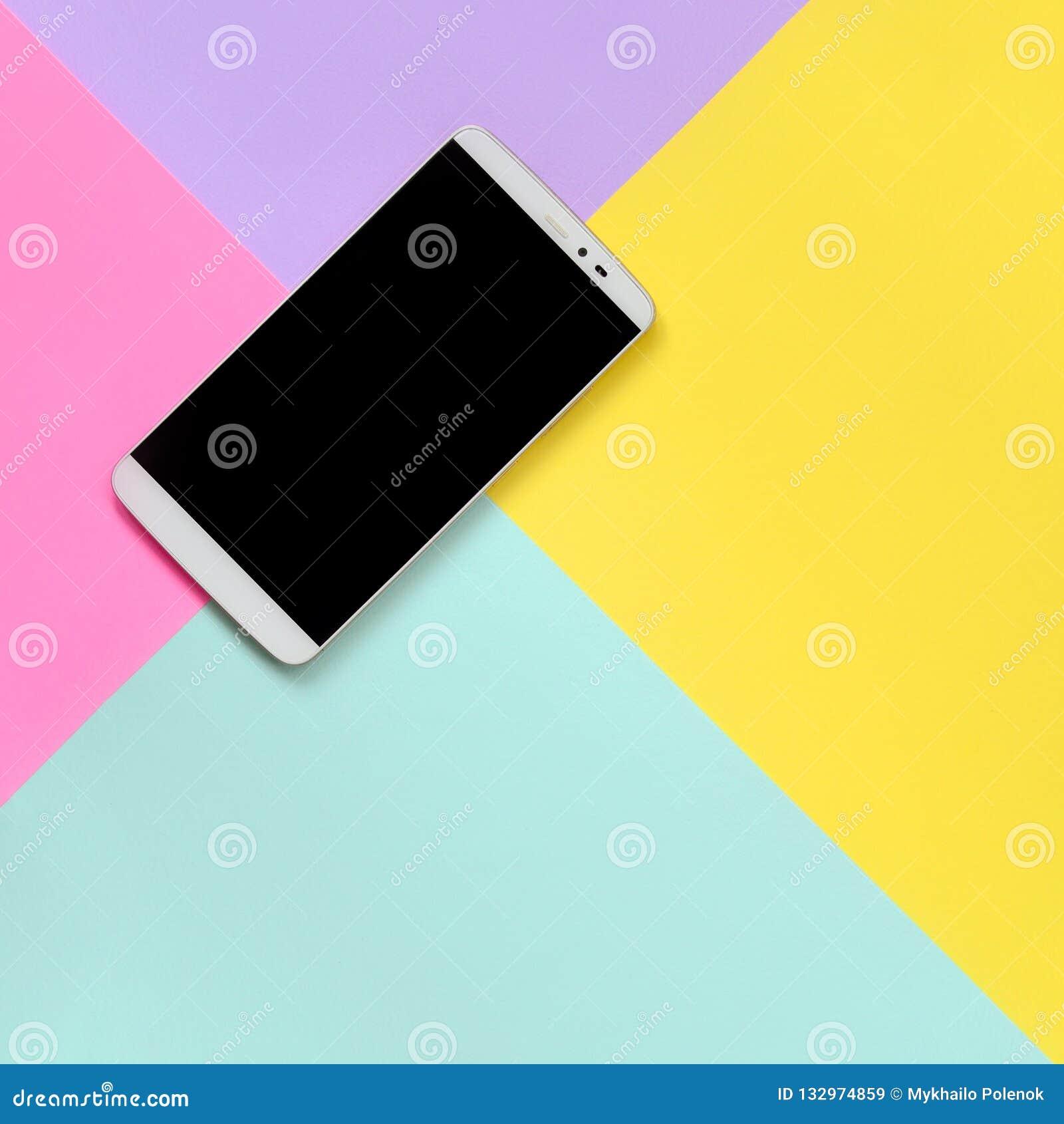 有黑屏幕的现代智能手机在时尚淡色蓝色,黄色,紫罗兰和粉色纸纹理背景在最小