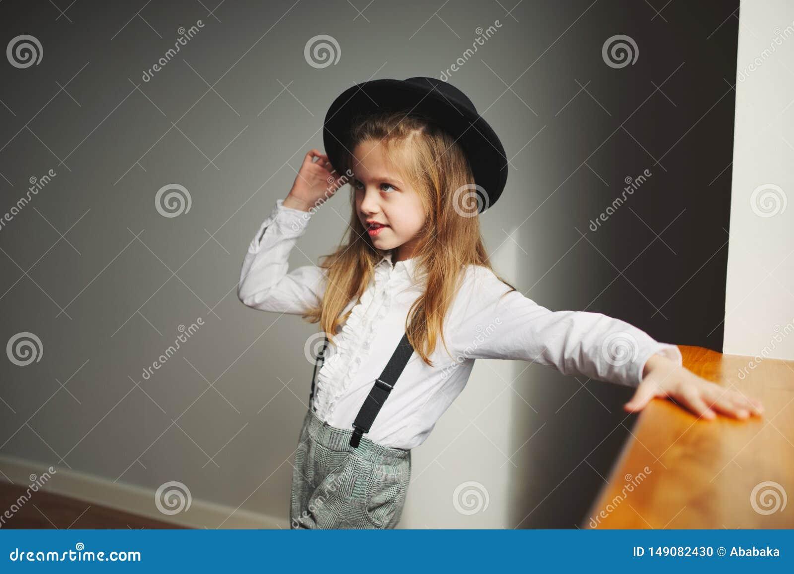 有黑帽会议的逗人喜爱的女孩在家
