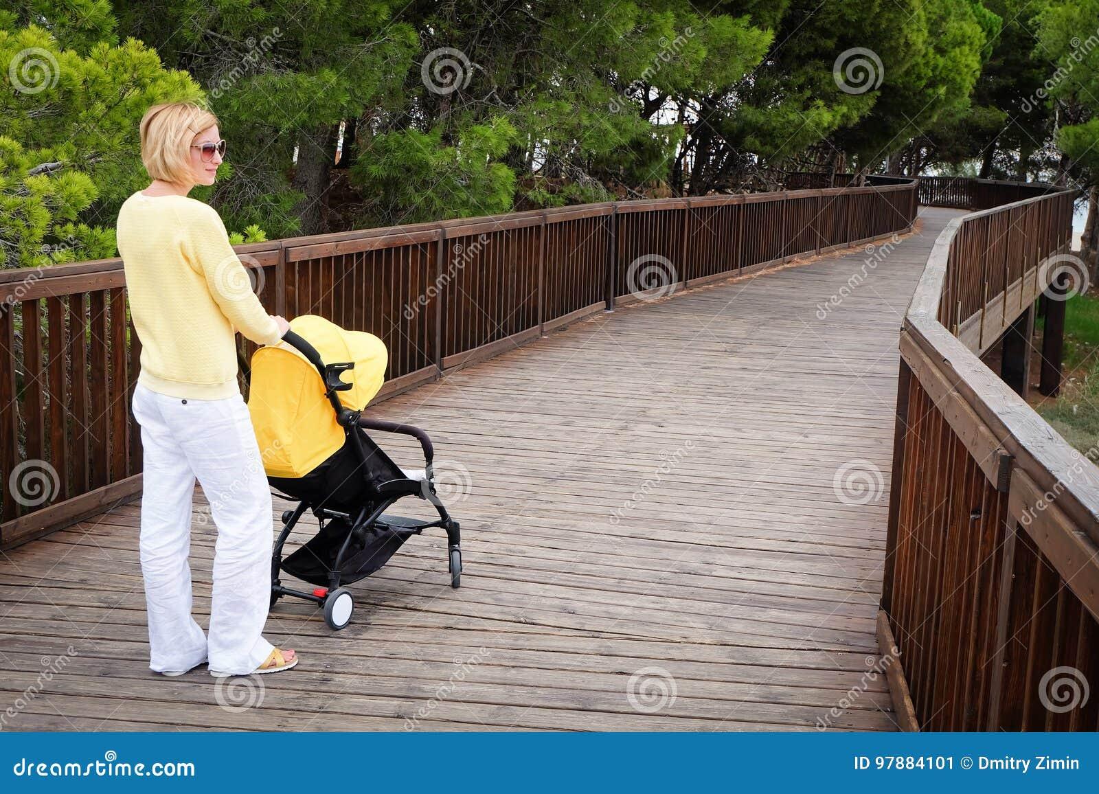 有婴儿推车的年轻母亲在公园