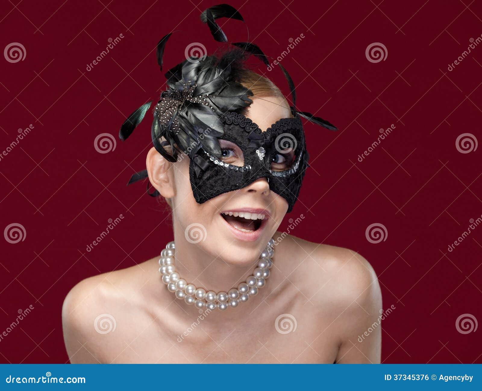 有黑化妆舞会面具的少妇与羽毛,隔绝在紫色.图片