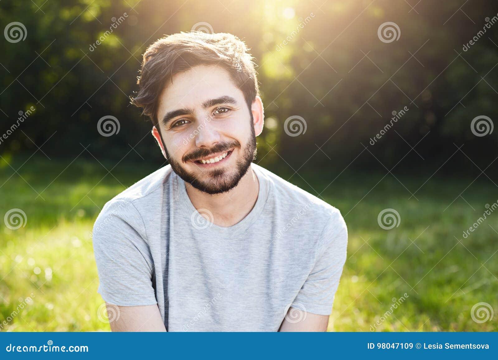 有黑发、厚实的眼眉、吸引人的穿偶然T恤杉的眼睛和胡子的年轻微笑的人坐在有的格陵兰好