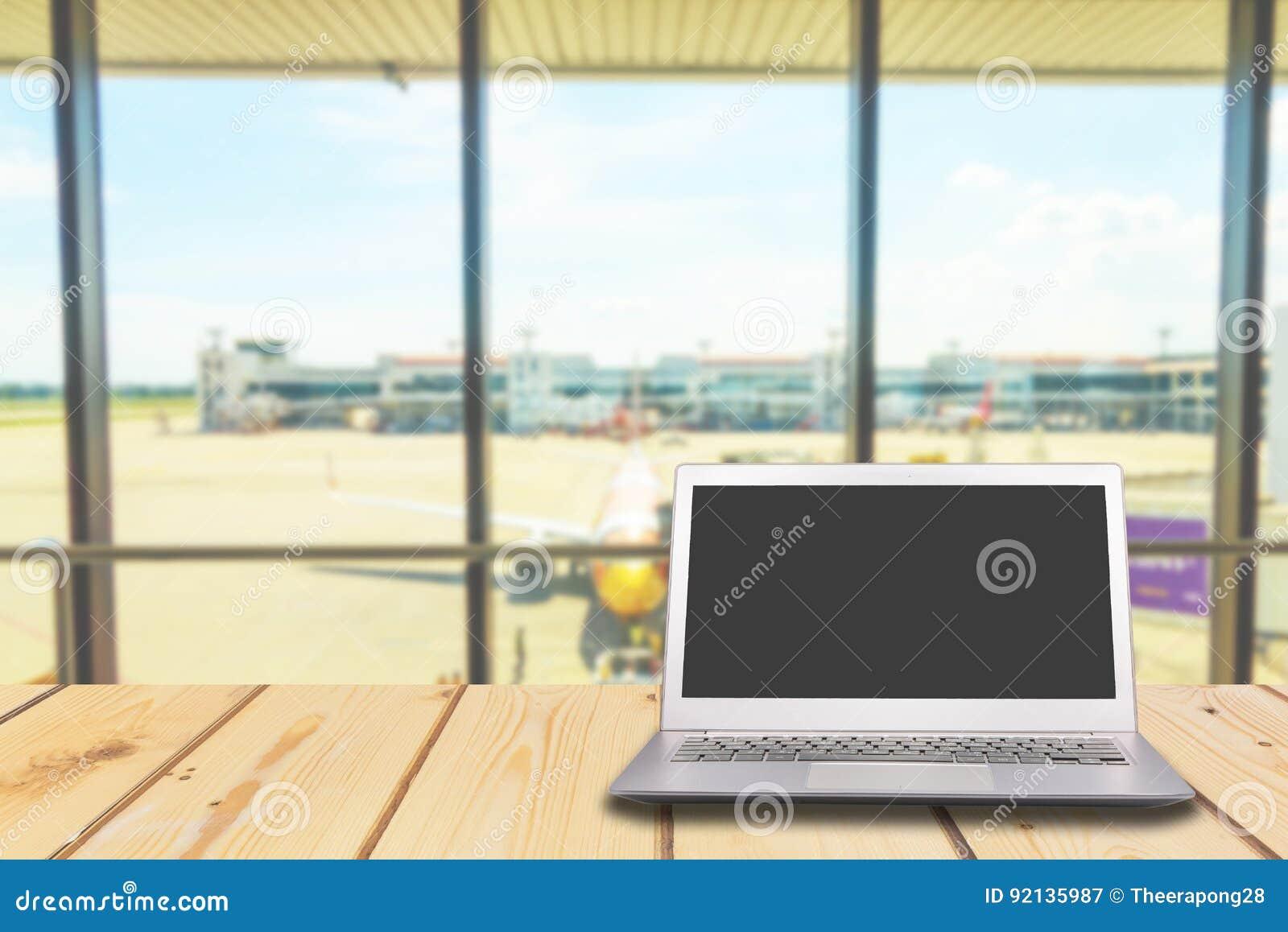 有黑屏的膝上型计算机在与机场的木桌上门ba的