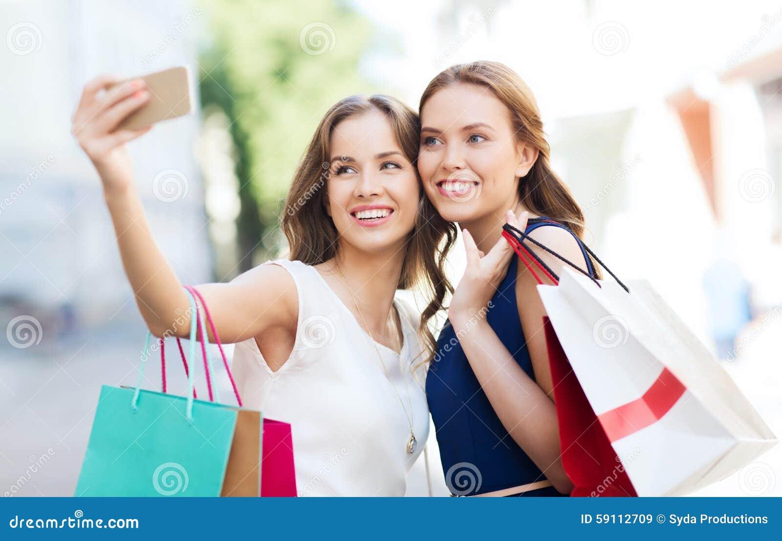 有购物袋和智能手机的愉快的妇女