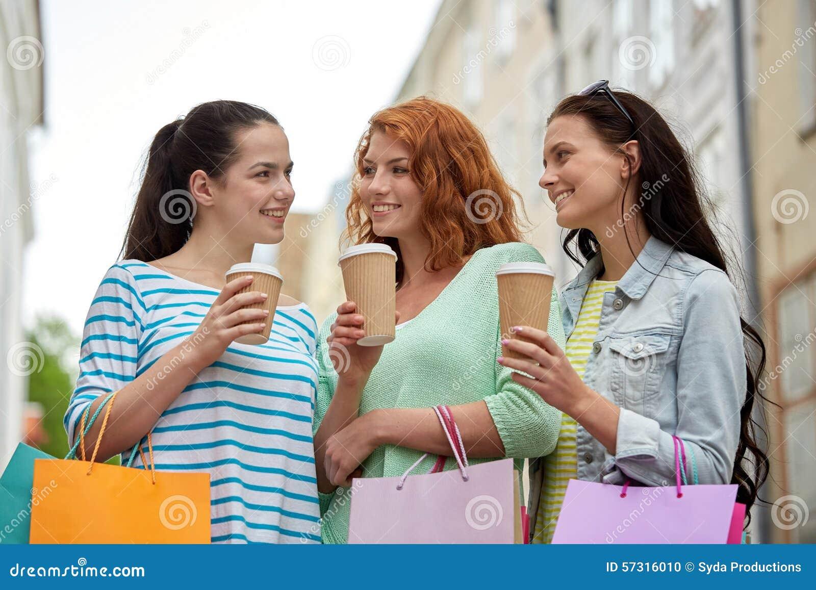 有购物袋的愉快的妇女和咖啡在城市