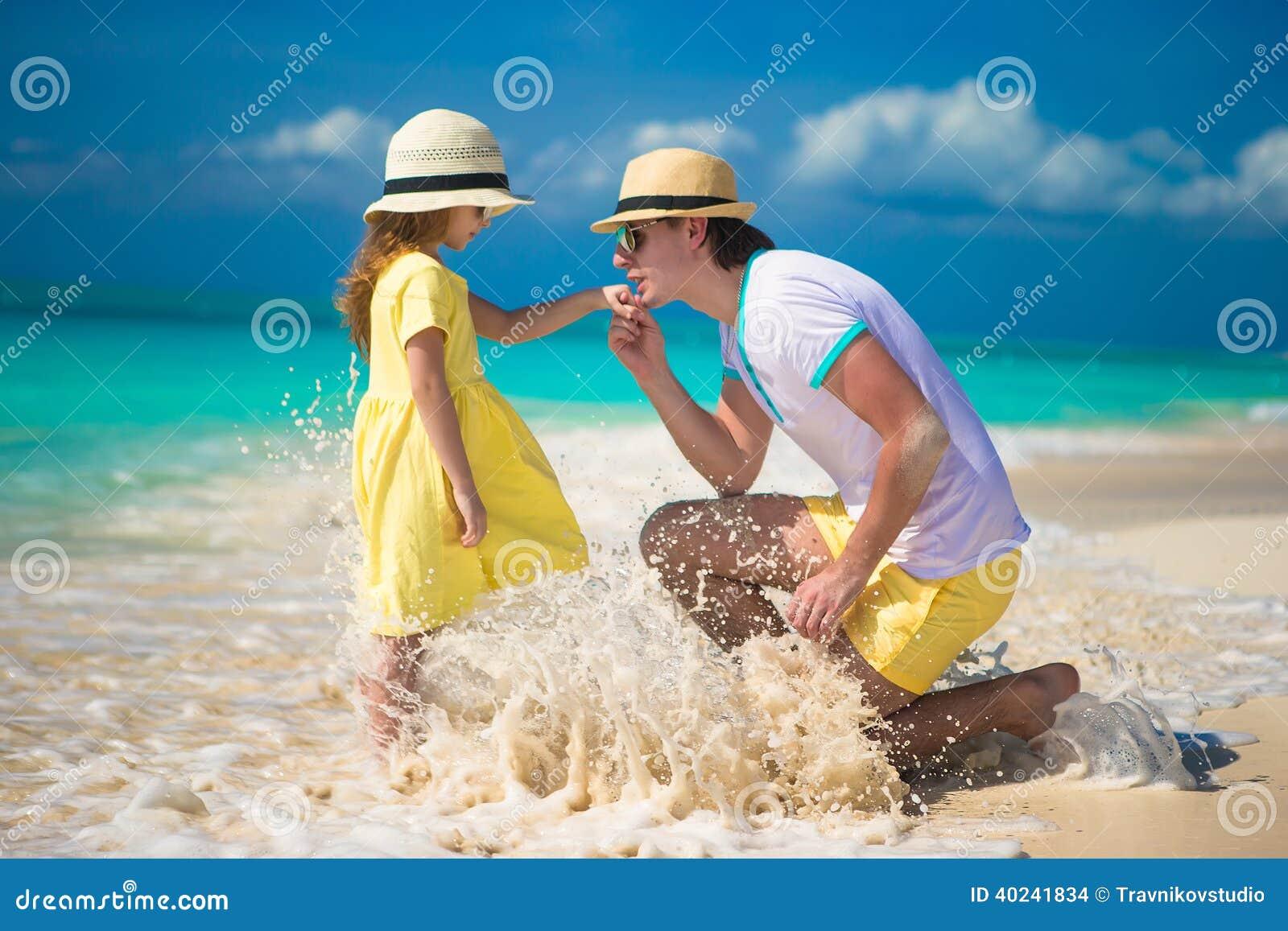 有他的享受海滩假期的小女儿的愉快的父亲
