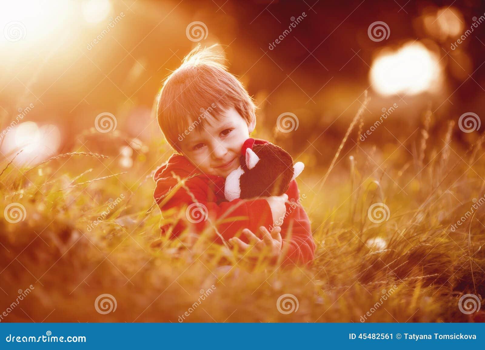 有他的女用连杉衬裤朋友的可爱的男孩,坐草坪