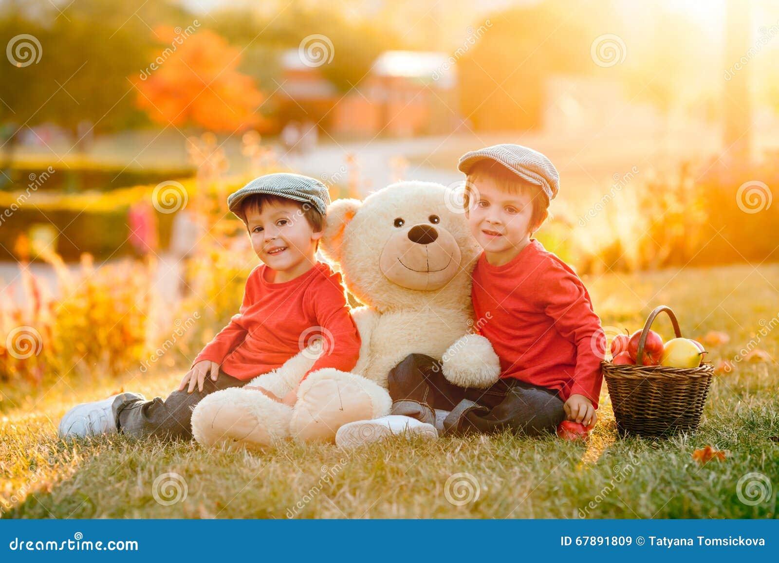 有他的玩具熊朋友的两个可爱的小男孩在公园