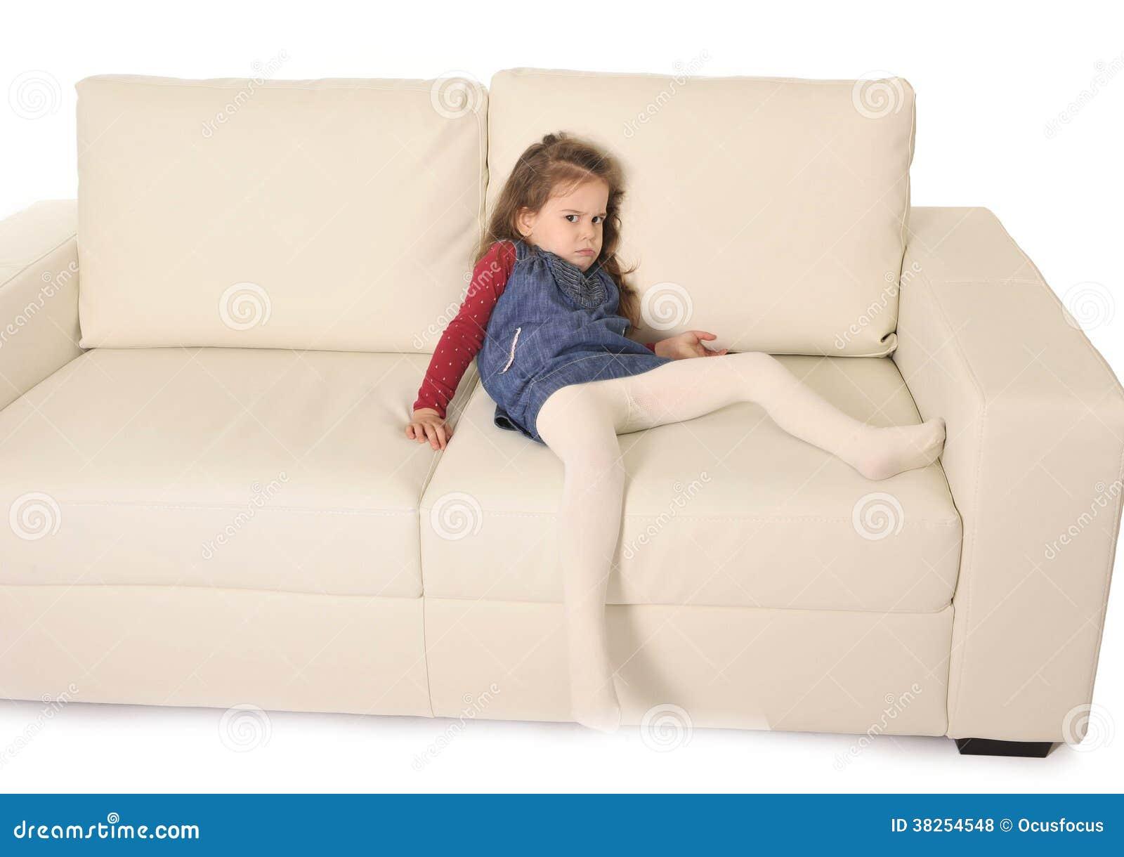 有说谎在长沙发的长的头发的愉快的可爱的小女孩嬉戏