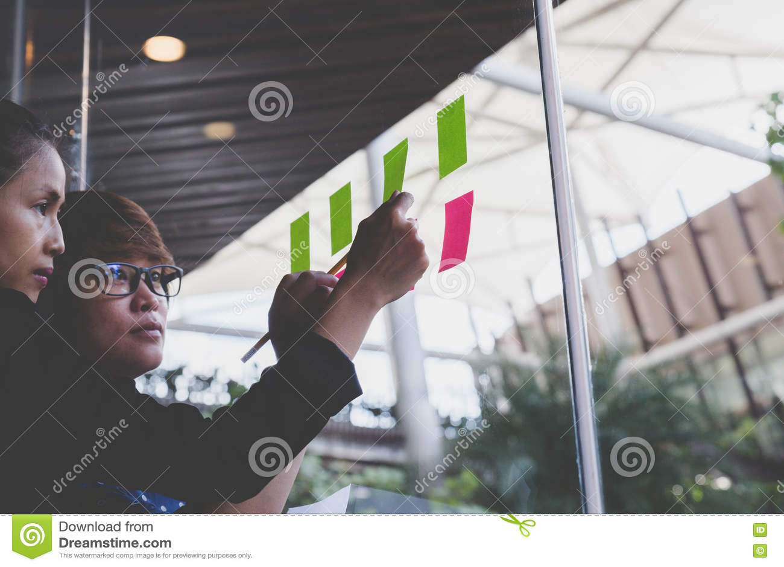 有黏附黏着性笔记的同事的年轻女实业家在gl