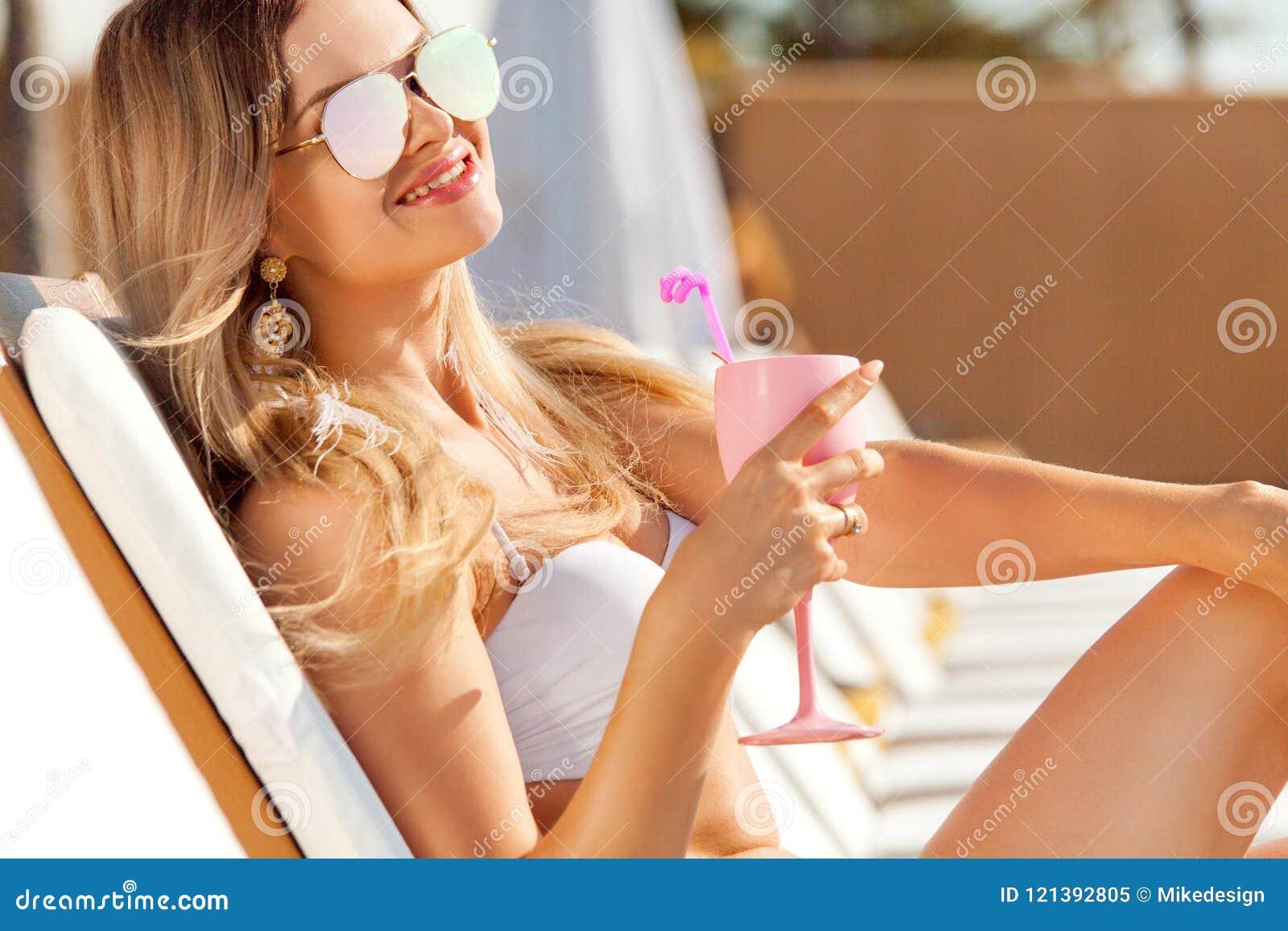 有coctail的少妇在海滩在夏天