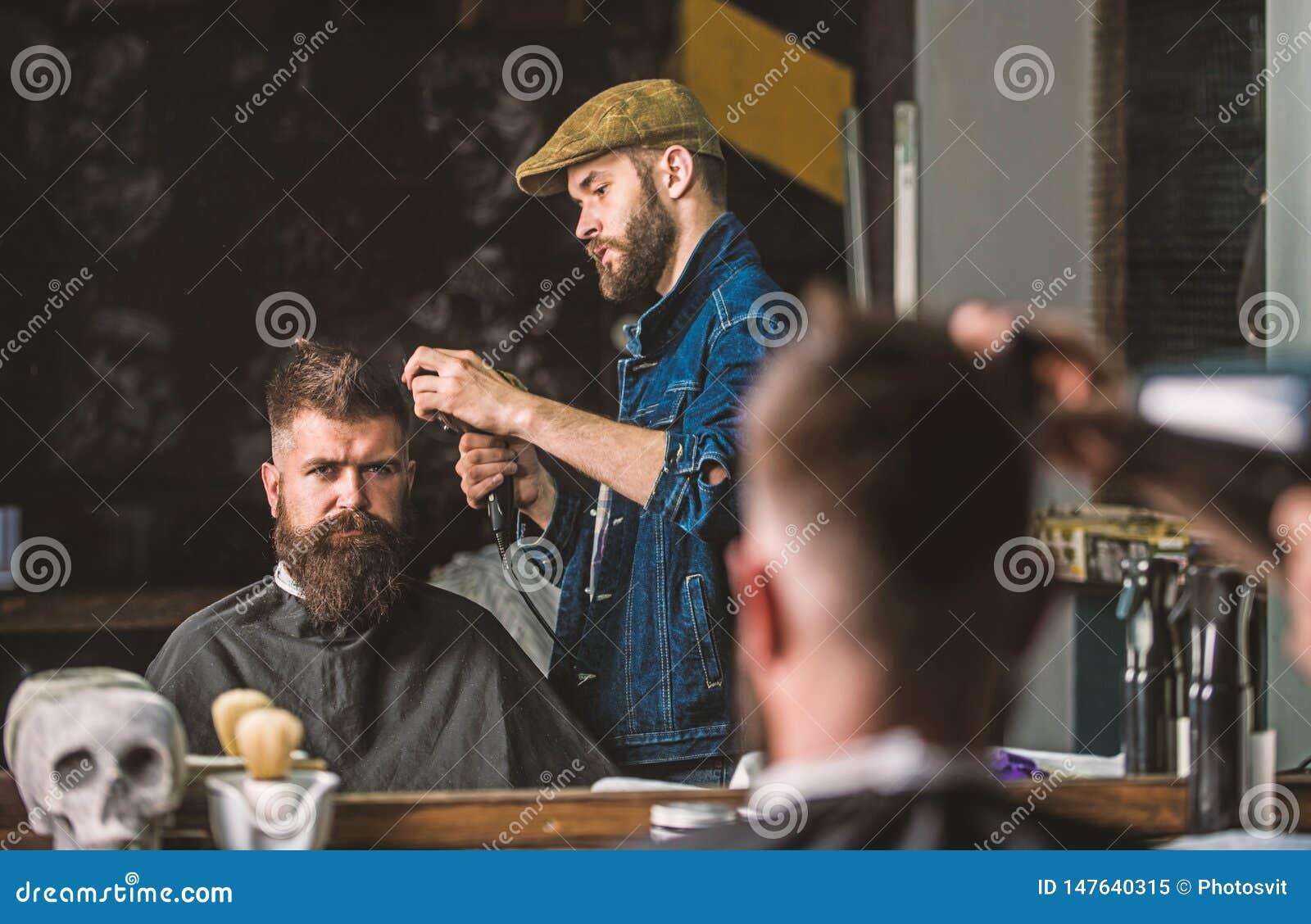 : 有hairdryer工作的理发师在有胡子的人的,理发店发型
