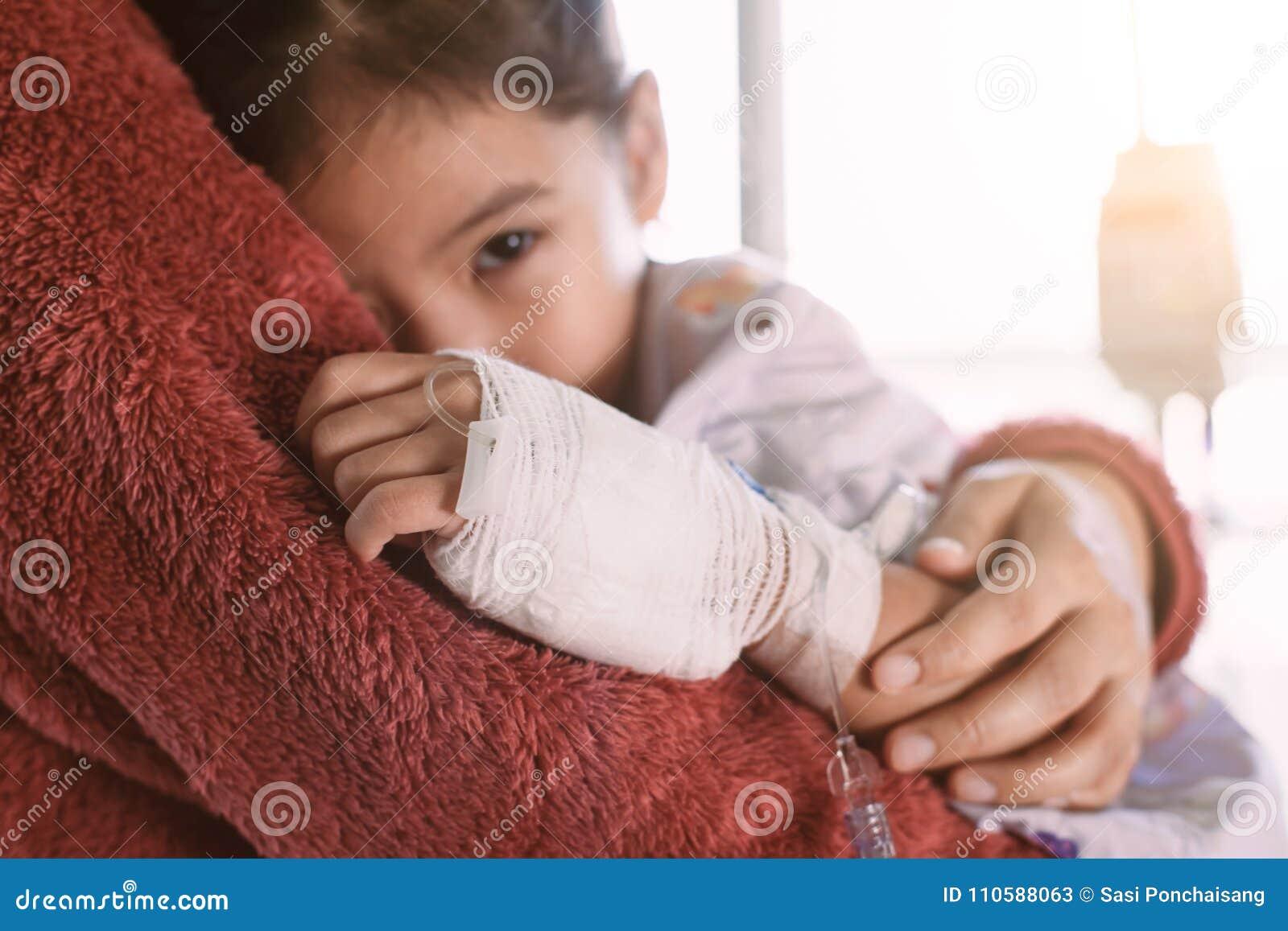 有IV拥抱她的母亲的解答的病的亚裔儿童女孩