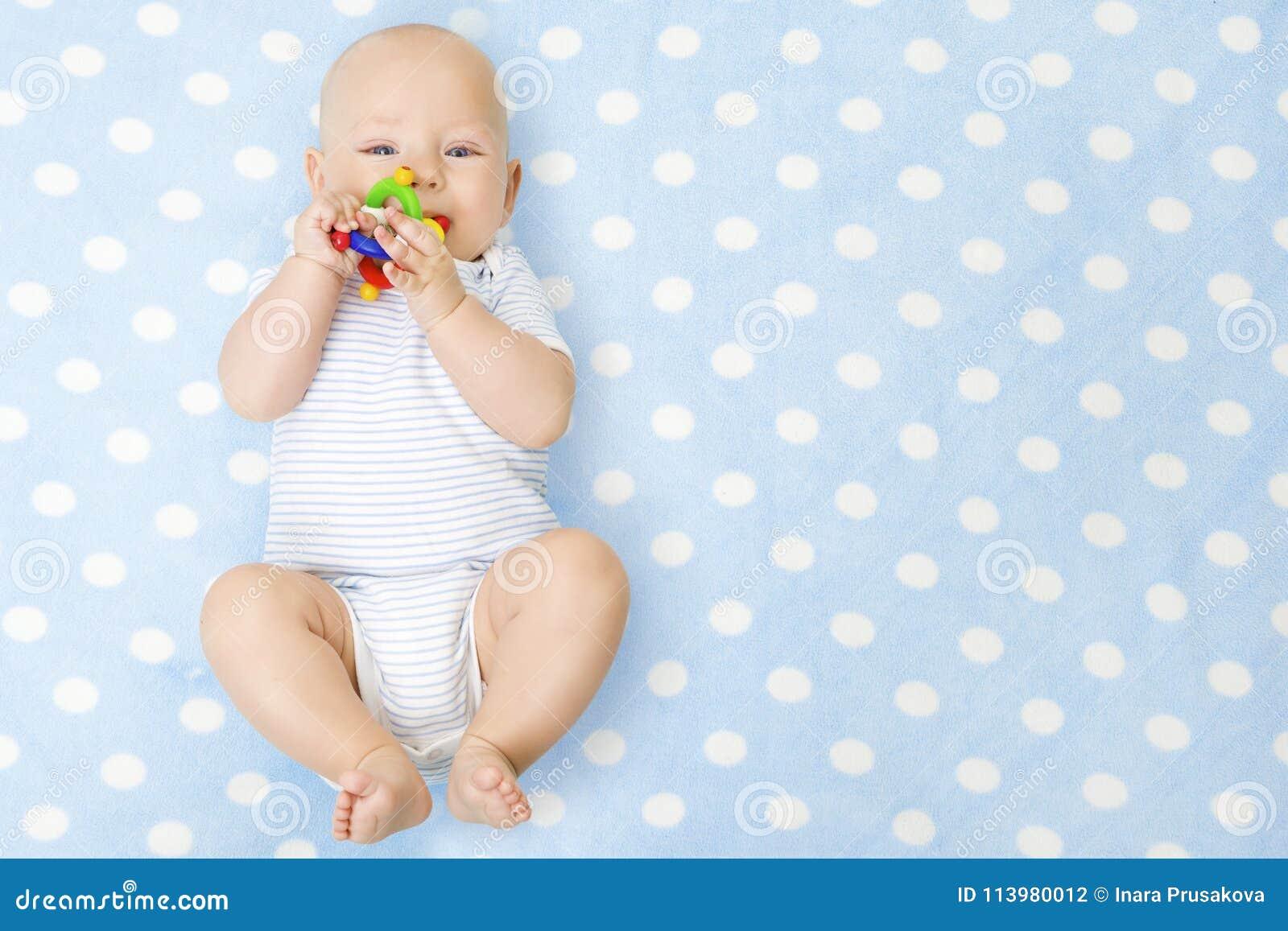 有Teether玩具的男婴在说谎在蓝色背景的嘴,愉快