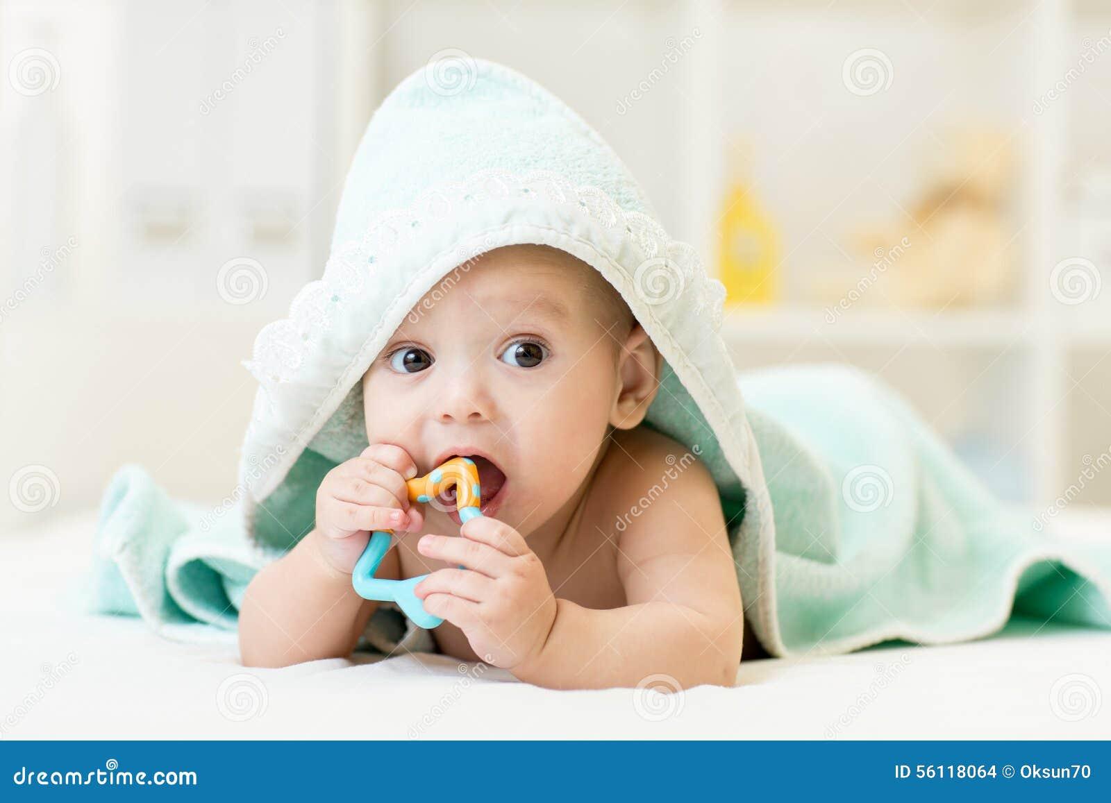 有teether的婴孩在沐浴毛巾下的嘴在托儿所