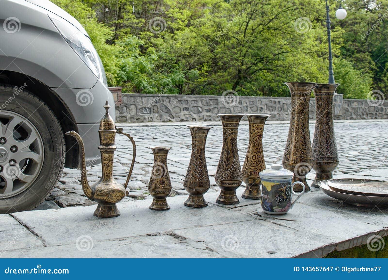 有tradiitional装饰品的传统东方黄铜手工制造水罐由一个摊贩的待售旧货市场的在Sheki: