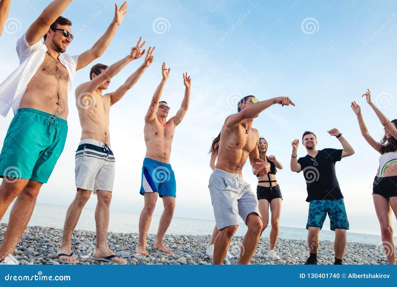 朋友在海滩跳舞在日落阳光下,获得乐趣,愉快,享用