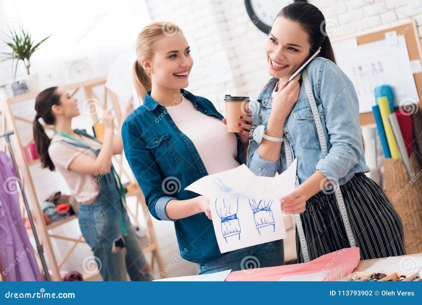 服装工厂的三个女孩 他们看图纸和饮用的咖啡