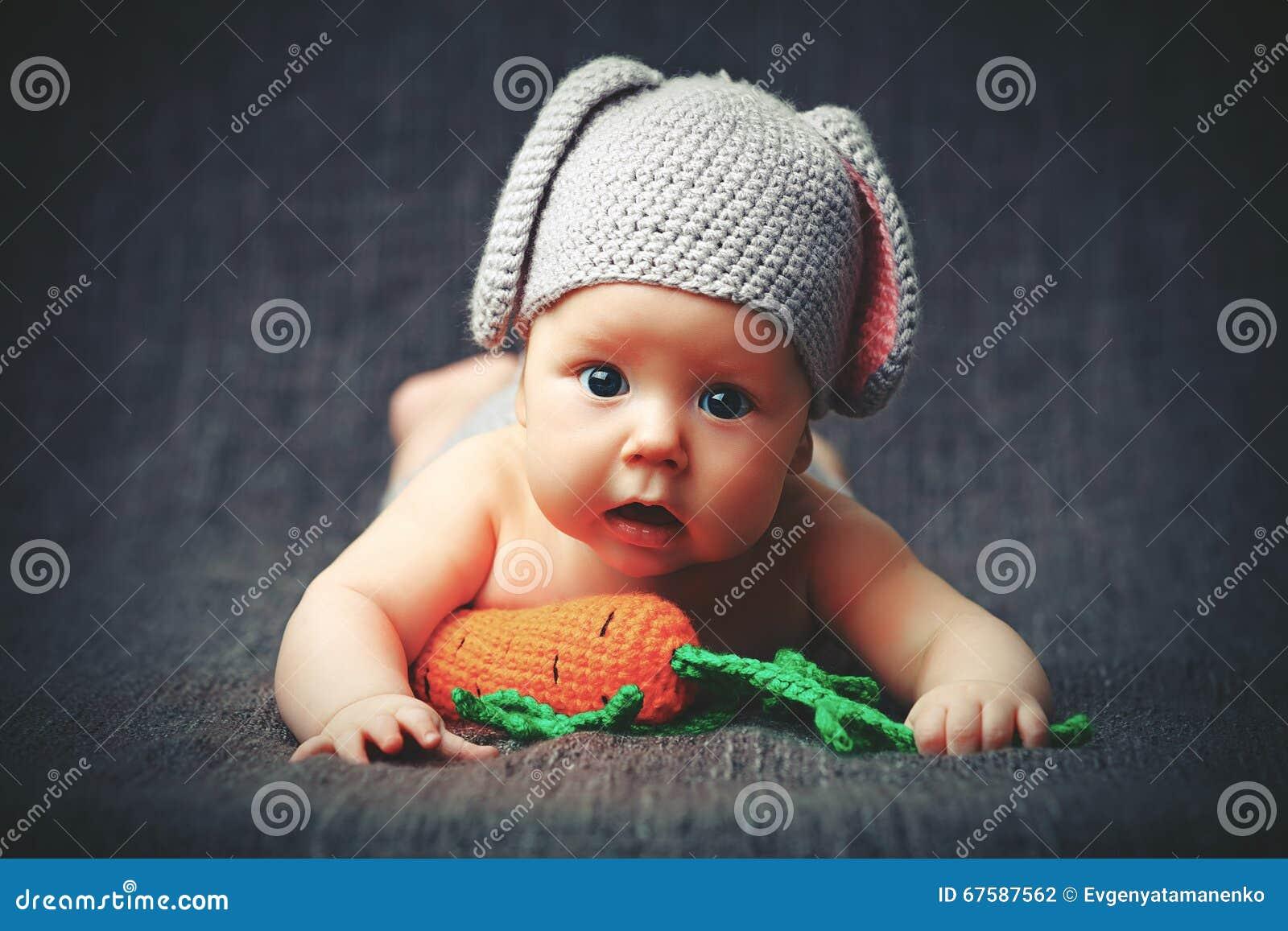 服装的愉快的小孩子一个兔子兔宝宝用在灰色的红萝卜