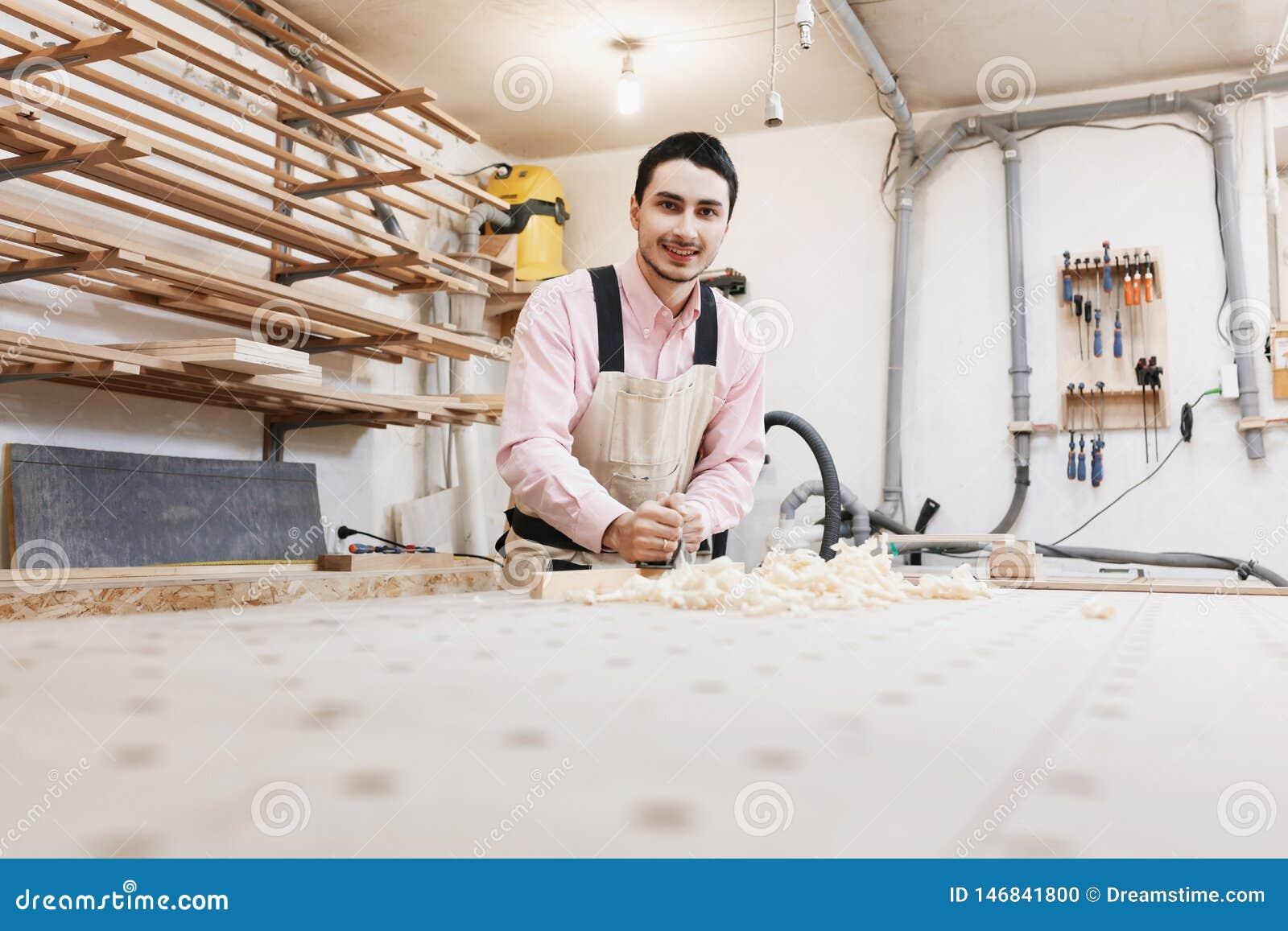 木匠与飞机和木板条一起使用在车间