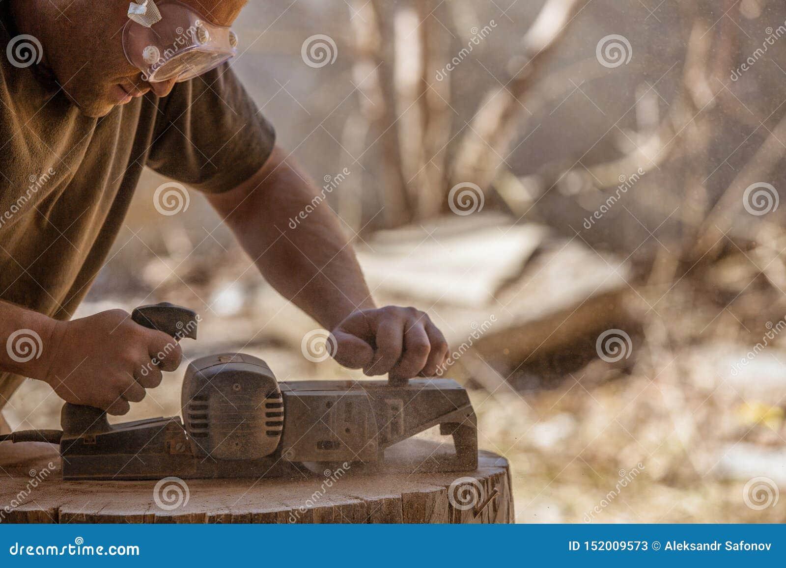 木匠露天与在木树桩的电整平机一起使用